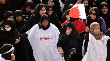 Anti-government protesters carry Bahraini flags during a march of thousands in 2011.