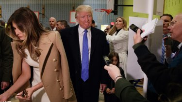 Republican presidential candidate Donald Trump, accompanied by his wife Melania, talks with reporters as he waits in line to vote.