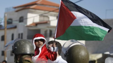 The Palestinian flag held by a child in the West Bank in 2013.