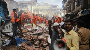 A rescue worker makes an announcement on a loudspeaker at the site of the building collapse in Mumbai.