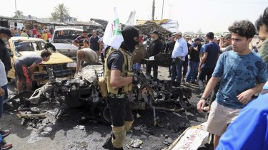 A masked member of an Iraqi Shiite fighters militant group called Kataib Peace Brigades, a Shiite militia group loyal to Shiite cleric Muqtada al-Sadr, centre, on the street with a flag after a suicide car bombing hit a crowded outdoor market in Sadr City on Tuesday.