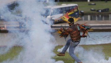 An indigenous man returns a tear gas canister to police outside the National Congress in Brasilia, Brazil, on Tuesday.