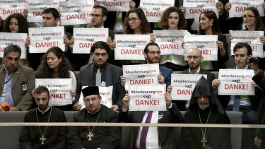 "Guests hold posters reading ""Recognition Now says thank you"" during a meeting of the German federal parliament."