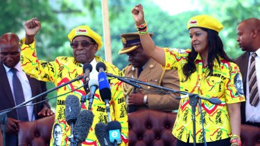 Zimbabwean President Robert Mugabe, left, and his wife Grace Mugabe chant the party's slogan during a solidarity rally in Harare last week.