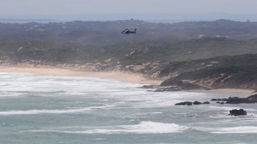 A search and rescue helicopter hovers over where two men went missing in waters off Cape Schanck on March 7.