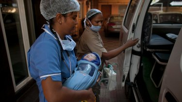 A newborn baby is transferred to an ambulance at surrogacy clinic in Anand, India, last year.