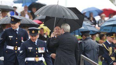 Bill Shorten and Kevin Rudd share an umbrella as they wait for the Prince of Wales and the Duchess of Cornwall to arrive at the Remembrance Day ceremony at the National War Memorial.