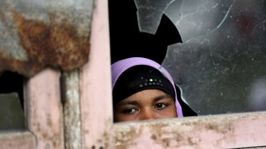 An ethnic Rohingya woman looks out from a window at a temporary shelter in Indonesia in May.