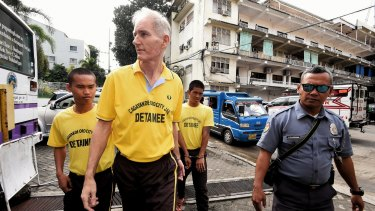 Peter Scully, foreground, arrives at the Cagayan De Oro court handcuffed to another inmate on the first day of his trial in September.