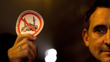 "A demonstrator holds a sticker with a crossed mosque symbol during a march against ""Islamification"" in Berlin."
