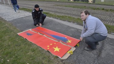 Policemen inspect Chinese flags defaced near Prague Castle on Saturday, ahead of the visit of Chinese President Xi Jinping.