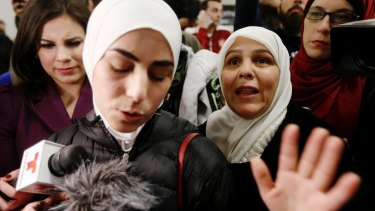 Mariam Yasin, left, translates for her mother Najah al-Shamieh, 55, from Syria, after immigration authorities released her.