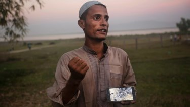 Osman Gani, a Rohingya man from Myanmar, shows a video clip that he shot on his mobile phone as he describes the recent violence standing on the bank of the Naf River, near a camp for Rohingyas near Cox's Bazar, Bangladesh.
