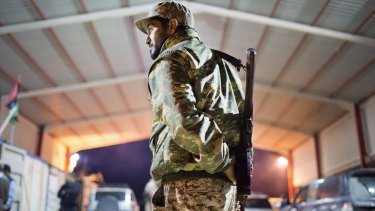A Libyan military soldier stands guard at the entrance of a town 110 kilometers from Sirte.