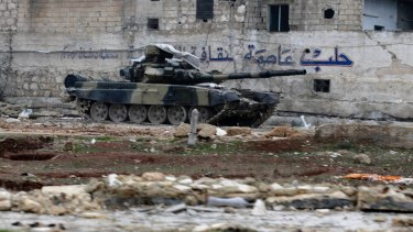 """A Syrian army tank is seen in front of a wall bearing the legend """"Aleppo is the capital of culture"""" in the east Aleppo neighbourhood of Tariq al-Bab earlier this month."""