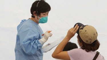 A nurse talks with a woman and child in a tent used as a waiting room for people being tested for MERS.