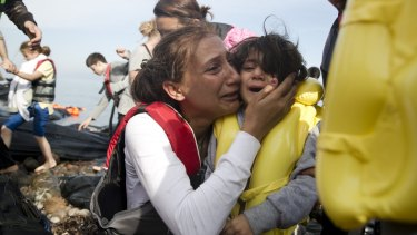A Syrian woman and her child react after they arrived with others from Turkey on the shores of the Greek island of Lesbos, on a inflatable dinghy on Sunday.