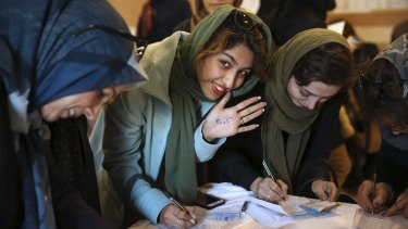 An Iranian voter shows her hand with numbers 30+16, a reformists slogan urging people to vote all reformists and moderate candidates, as she fills out her ballot in a polling station in Tehran, Iran on Friday.