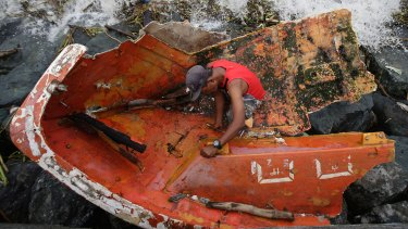Filipino Joybin Marayo, 58, salvages metals on a damaged boat that was washed ashore by strong waves brought about by typhoon Haima in Manila.