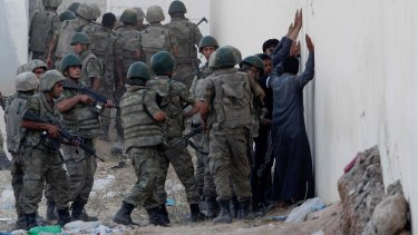 Turkish soldiers detain men near the Akcakale crossing gate between Turkey and Syria on Monday. From Syria, the men were suspected of being IS militants.