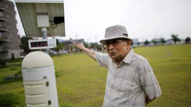 Atsushi Hoshino, a 87-year-old Hiroshima atomic bombing survivor, former college professor and ex-president of Fukushima University, beside a radiation meter, near his home in Fukushima.