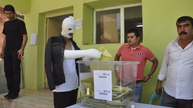 Wounded in Saturday's attack against the pro-Kurdish Peoples' Democratic Party (HDP) rally in Diyarbakir, a Turk casts his ballot on Sunday.