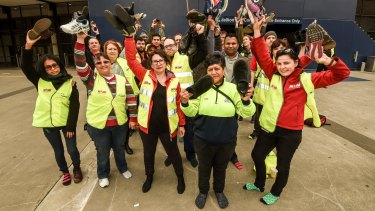 National Union of Workers members take off their boots in solidarity with women AFL players at Etihad Stadium.