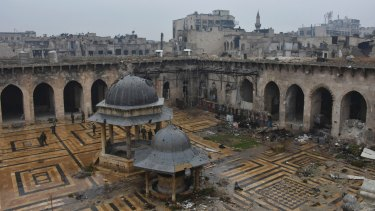 Syrian troops and pro-government gunmen marching walk inside the destroyed Grand Umayyad mosque in the old city of Aleppo.