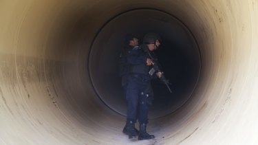 Federal police inspect a drainage pipe outside the Altiplano maximum security prison in Almoloya, west of Mexico City on Sunday.