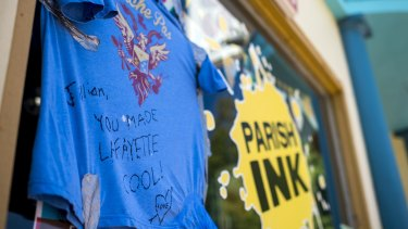 A shirt with a message dedicated to shooting victim Jillian Johnson hangs on the storefront window of Johnson's store Parish Ink in downtown Lafayette.