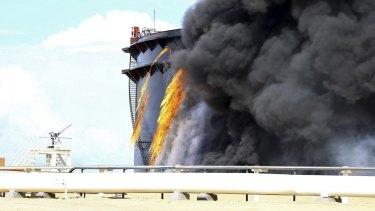 Black smoke billows out of a storage oil tank in the port of Es Sider in Ras Lanuf after a rocket hit it.