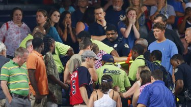 Shocked fans watch as paramedics carry the man from the stadium.