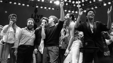 From left, George Michael of Wham!, concert promoter Harvey Goldsmith, Bono of U2, Paul McCartney, concert organiser Bob Geldof and Freddie Mercury of Queen join in the finale of the Live Aid famine relief concert, at Wembley Stadium, London in 1985.