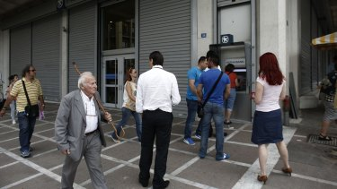 Bank customers queue to withdraw cash from an ATM in Athens, Greece, on Friday.