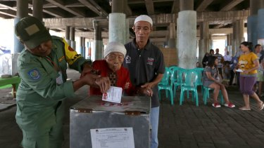 Electoral workers help an elderly woman cast her ballot at a makeshift polling station under a bridge.