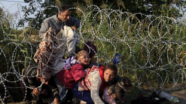 Syrian migrants wriggle under barbed wire to get into Hungary on Thursday.
