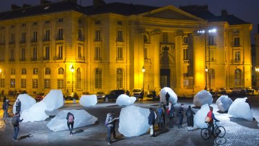 Visitors walk through ice blocks as part of the sculpture Ice Watch, by Danish artist Olafur Eliasson, as part of the Paris climate talks.