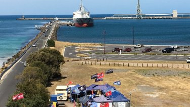 The MV Portland moored at Portland's Lee breakwater, supported by a protest camp in the foreground.
