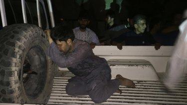 A wounded man rests on a vehicle after a suicide attack on a mosque in Herat, Afghanistan.