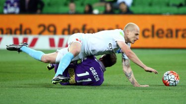 Down but not out: Aaron Mooy of Melbourne City is brought down in a challenge by Richard Garcia of Perth Glory.