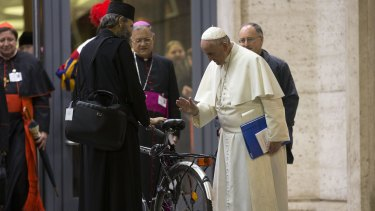 Pope Francis blesses the bicycle of a prelate participating in the Synod at the Vatican on Wednesday.