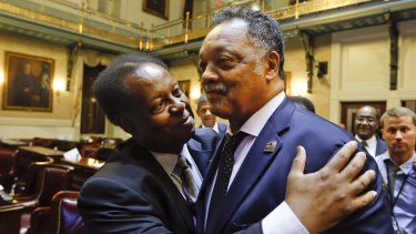 South Carolina Representative Carl Anderson left, embraces Reverend Jesse Jackson after the House approved a bill removing the Confederate flag from the Capitol grounds in South Carolina.