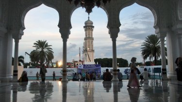 People gather at Baiturrahman Grand Mosque at dusk in Banda Aceh on Friday.