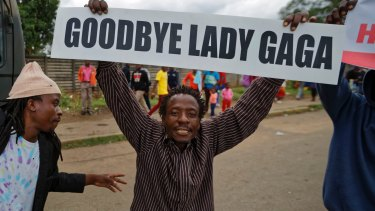 A protester demanding Robert Mugabe's resignation carries a placard referencing the excesses of Mugabe's wife, Grace.
