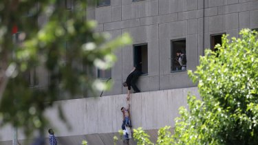 A man hands a child to a security guard from Iran's parliament building in Tehran after an attack on the complex on Wednesday.