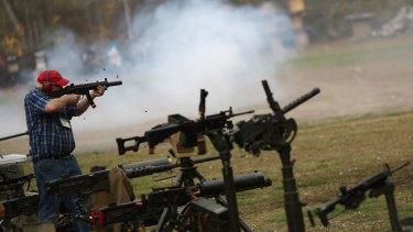 Firing a suppressed Heckler & Koch MP5 submachine gun at the Knob Creek Machine Gun Shoot in Kentucky.