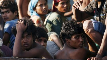 Illegal migrants and asylum-seekers aboard a boat tethered to a Thai navy vessel on Saturday.