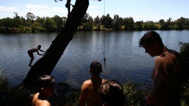 Boys from Penrith cool off in the Nepean River on Saturday.