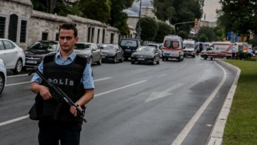 A police officer secures the area around the scene of the bomb attack.