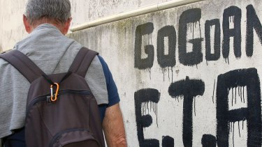 A man walks past graffiti reading 'ETA  Basque country and Freedom', in Sare, south-western France, on April 7, 2017.